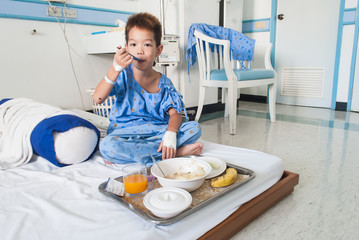 Asian patient boy with saline intravenous (iv) on hospital bed.