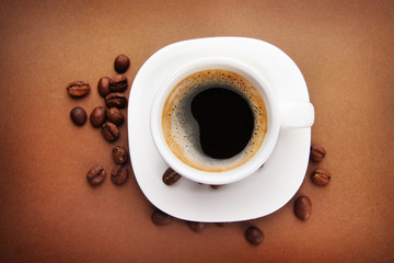 Cup of coffee with coffee beans on brown background