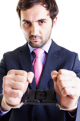 Serious businessman with shackles on his hands