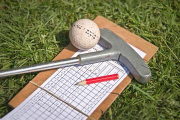 Balle de golf, club et fiche de score