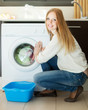 Home laundry. Woman using washing machine