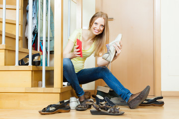 Happy woman cleaning footwear