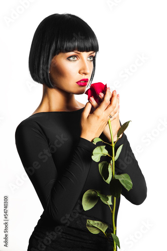 Sensual adult female with red rose on white background in studio