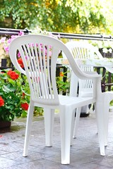 White plastic chairs and table on the terrace in the garden.