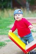 baby boy age of 10 months stands by teeter-totter