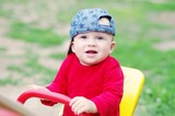baby age of 10 months teeters outdoors in summer