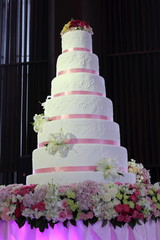 wedding cake with pink ribbon and flowers