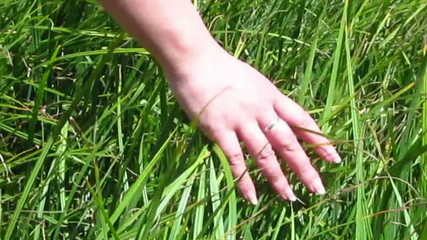 The female hand slides on a green grass
