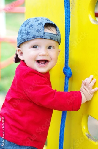 happy smiling baby boy on playground in summertime