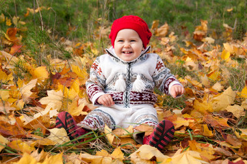 Little cute baby girl on a background of autumn leaves