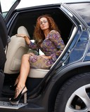 Beautiful redhead woman stepping out the car