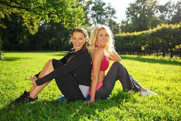 Two smiling athletic girls sitting on a grass in a park