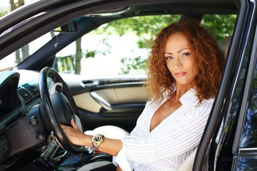 Beautiful  redhead woman behind steering wheel