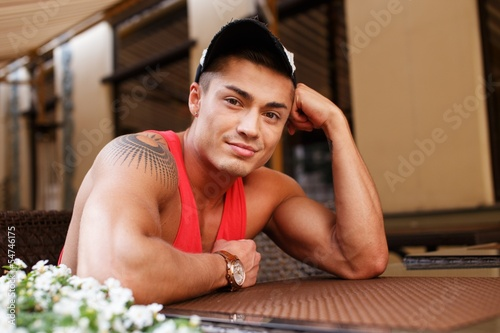 Stylish young man in  cap sitting behind table
