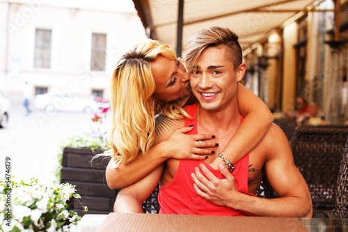 Stylish couple behind table in a summer cafe