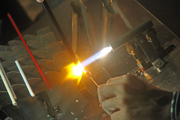 Glazier with gas torch lit while blending a piece of glass 1