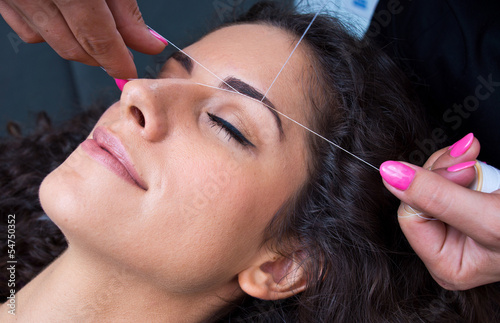 woman on facial hair removal threading procedure - 54750352
