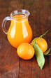 Full jug of tangerine juice, on wooden background