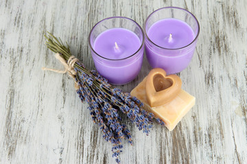 Lavender candle with fresh lavender, soap on wooden background