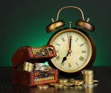 Antique clock and coins on wooden table on dark color
