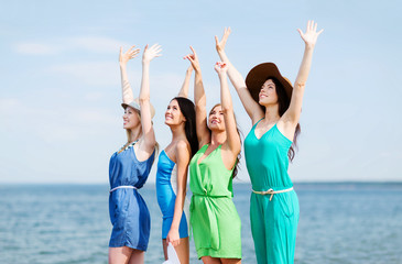 girls looking at the sea with hands up