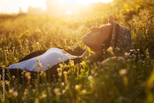 Happy girl lies among the wild flowers