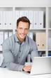 lächelnder mann mit laptop im büro