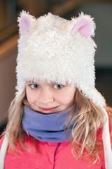 Little blond girl in fun white artificial fur hat