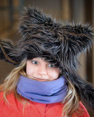 Little blond girl in fun artificial fur hat