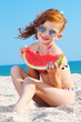 Happy child on the sea with watermelon