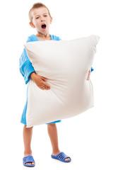 Yawning child boy holding pillow going to sleep