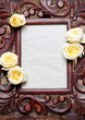 Wooden frame decorated with yellow, pastel roses. Copy space