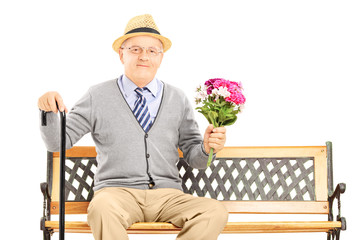 Senior gentleman sitting on a wooden bench and holding a bunch o