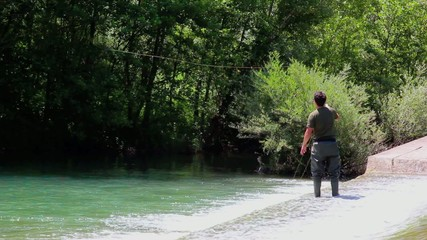 Fisherman casting during fly fishing with green wood background