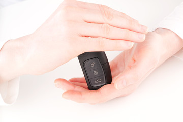 Insurance - hands protecting a car key