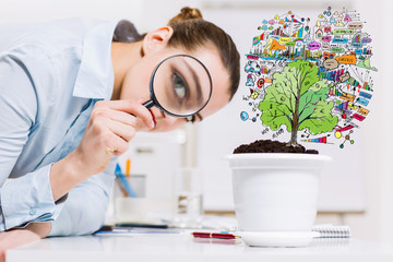 Businesswoman examining sprout