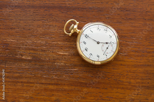 Gold Pocket watch on wood background