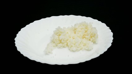 Steamed jasmine rice on a white dish is being prepared