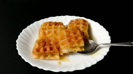 Baked waffle topped with honey is ready to eat with spoon