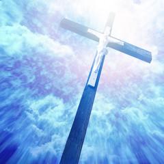 cross in sunrays against cloudy sky
