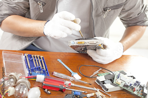 repair man, engineer fixing computer part on work table