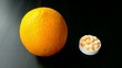 An orange is compared to the bowl of vitamin c supplements