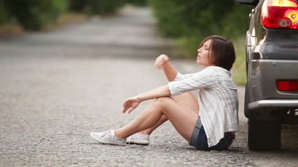 Sad pretty girl sitting on  the road after car accident