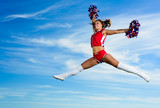 Young cheerleader in red costume jumping