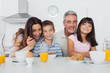 Beautiful family eating breakfast in kitchen together