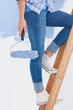 Woman holding paint roller climbing ladder