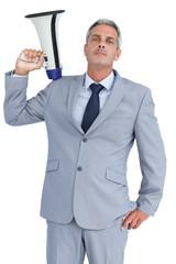 Businessman posing with loudspeaker on his shoulder