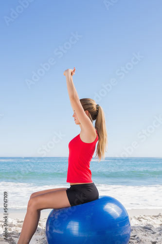 Fit woman sitting on exercise ball stretching arms