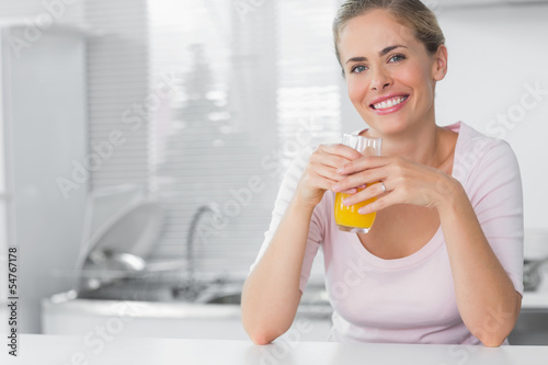 Cheerful blonde having orange juice