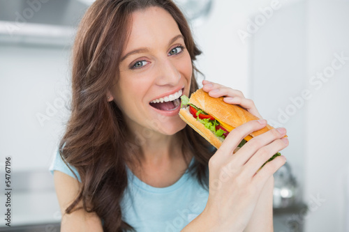 Cheerful brunette eating sandwich